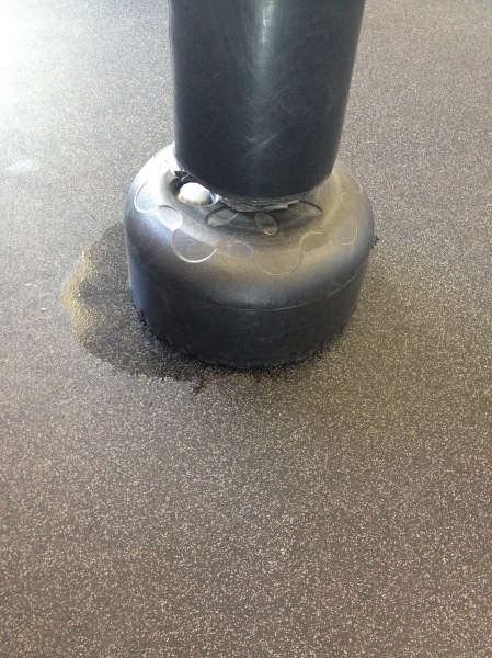 One of numerous standing punching bags leaking water onto rubber floor at Glen Iris. No mop available to clean up spill. Out of twenty such bags, six or seven leak in this way. After the class, the bags are moved away and spills are left behind.